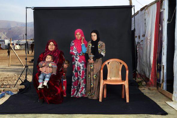 Gente, Tercer Premio, fotografías individuales Dario Mitidieri, Italia, CAFOD, Retratos de familias perdidas 15 de diciembre de 2015. Una familia siria posa en el campo de refugiados Beqaa Valley junto a una silla que representa a un miembro de su familia desaparecido. Según ACNUR, a finales de 2015, más de 370,000 refugiados sirios viven en el campo Beqaa Valley, cerca de la frontera Siria..