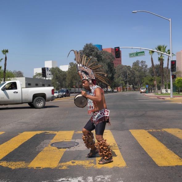 Un mejicano cruza un paso de peatones realizando una danza tradicional en Tijuana, México.