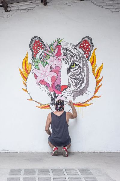 El artista dibujando su mural 'La máscara del tigre'.