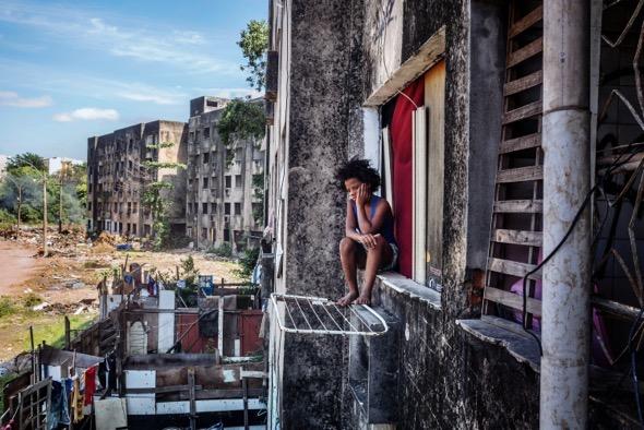 La joven Eduarda sentada junto a su ventana observa la calle. Vive en uno de los edificios nunca terminados de una promoción no lejos de Río de Janeiro. Es parte de los llamados sin cara y sin tierras. La cara menos amable de un Brasil que se gasta billones en eventos deportivos como los juegos Panamericanos, los Juegos Olímpicos o la Copa de la FIFA, pero esconde a las personas más desfavorecidas. Foto: Peter Bauza.