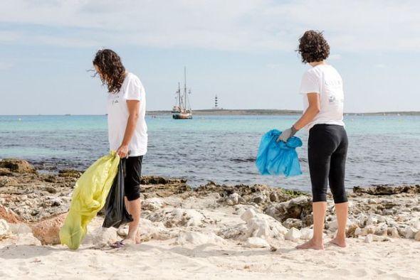 Dos participantes del Proyecto Libera de recogida de basuras en la naturaleza.