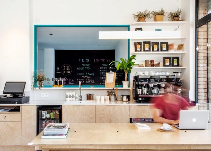 Cafeteria con mesas y taburetes de madera y ventana turquesa. Hubbub Family Fit Club.