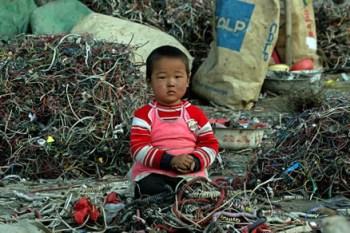 Niño rodeado de chatarra electronica