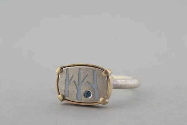 silver and gold ring with blue topaz on grey background