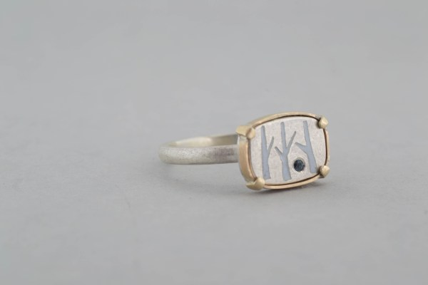 Side view of silver and gold birch tree ring on grey