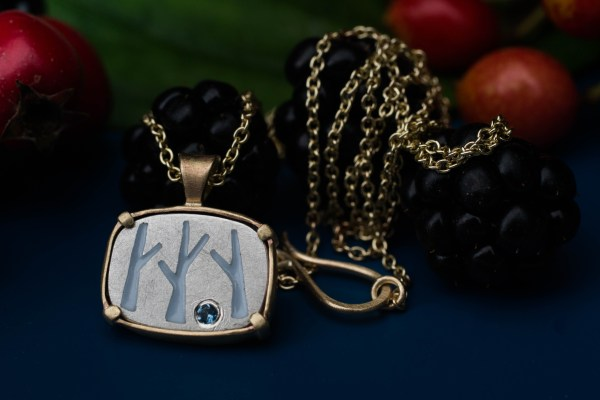 Birch tree necklace on blue bacrground with balckberries and gelder and leaf