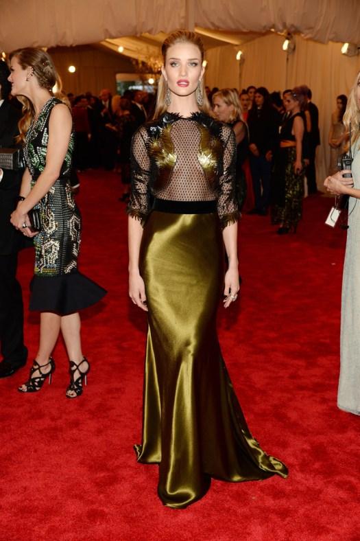 Rosie Huntington-Whiteley con un original diseño de Gucci con falda satinada, top de rejilla transparente y plumas cosidas estratégicamente.
