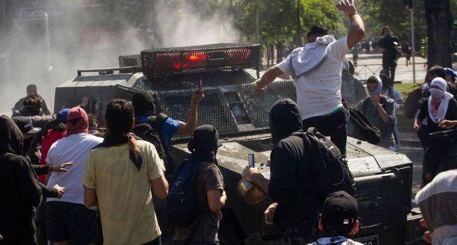 Los manifestantes rodean un vehículo de la policía en Santiago de Chile. (AFP / CLAUDIO REYES).