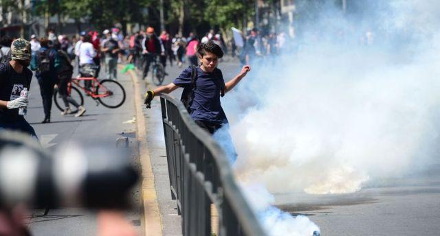 Un manifestante patea una bomba lacrimógena durante una protesta en Santiago. (AFP / Martin BERNETTI).