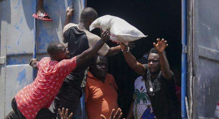 Un hombre arroja una bolsa de arroz desde el remolque de un camión lleno de suministros de socorro, superado por residentes en Vye Terre, Haití. (AP Photo / Fernando Llano)