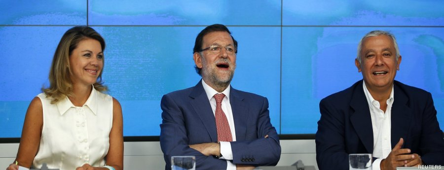 Spain's Prime Minister Rajoy reacts next to People's Party members Cospedal and Arenas at the start of a meeting in Madrid