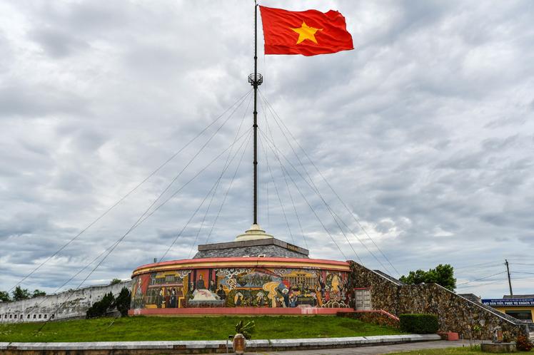 Sobre el mástil del monumento, la única bandera que ondea en Vietnam desde 1975 (orilla norte)
