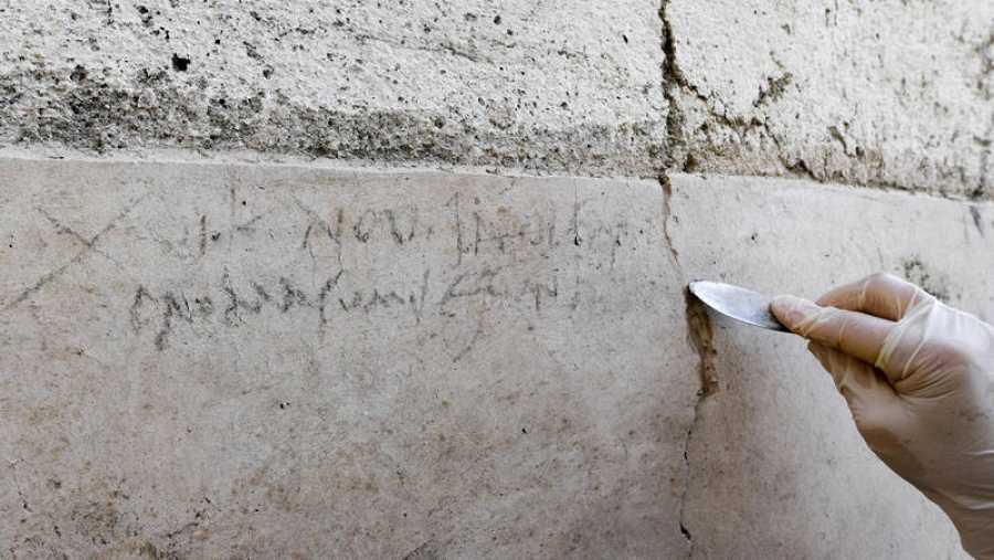 Una arqueóloga señala la inscripción de una pared encontrada en una excavación en Pompeya, Nápoles.