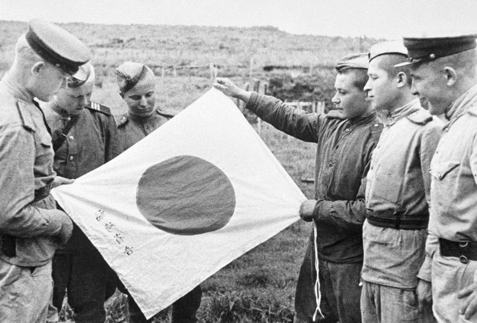 Soldados soviéticos contemplan la bandera abandonada por los soldados japoneses durante su retirada.