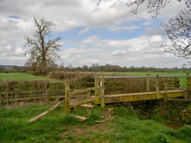 a stile and wooden bridge on a footpath