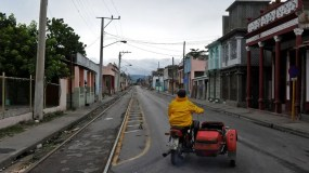 A Cuban drives a motorcycle along a street of Guantanamo city, Cuba on October 4, 2016 ahead the arrival of Hurricane Matthew. The most menacing storm in the Caribbean in nearly a decade, Matthew began battering Haiti late Monday with strong winds and rising sea levels, before barreling ashore some 250 miles west of the capital Port-au-Prince. / AFP / YAMIL LAGE
