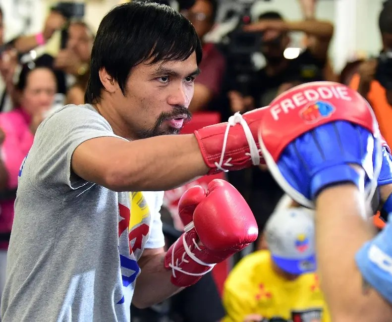 Boxer Manny Pacquiao spars with his coach Freddy Roach during a training session at the Wild Card Boxing Club in Hollywood, California on April 15, 2015. The Filipino Congressman and world champion boxer will fight Floyd Mayweather in Las Vegas, Nevada, on May 2 in what is being billed as the 'Fight of the Century', between the first and only eight-division world champion Pacquiao and undefeated five-division world champion Mayweather. AFP PHOTO / FREDERIC J. BROWN