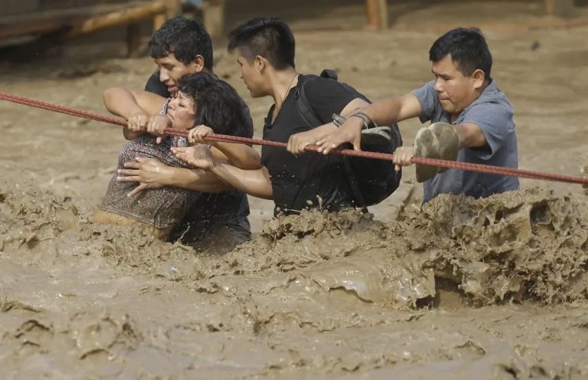 Un grupo de personas atrapadas por una inundación se aferran a una soga hasta ponerse a salvo en Lima, Perú. Las intensas lluvias, desbordes de ríos, avalanchas de lodo e inundaciones provocadas por el fenómeno climático El Niño Costero son peores en algunas zonas que hace dos décadas, afectan a más de la mitad de Perú y mataron a 72 peruanos desde inicio de año. (AP Foto/Martin Mejia)