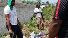 Agentes policiales vestidos de civil junto al cadáver de uno de los presos que escaparon de la cárcel de San Pedro de Macorís. El hombre estaba esposado.