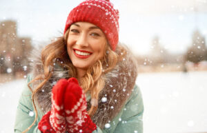 Woman with long wavy hair wearing a winter hat and gloves in the snow and smiling.