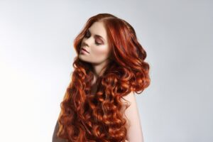 A woman with very long, thick, curly red hair.