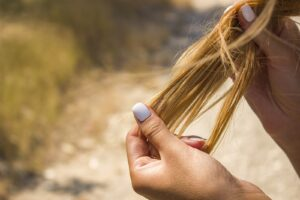 A person holding strands of dry hair