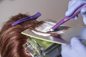 A hairdresser applying dye to red hair.