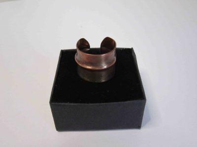 Fold formed copper ring resting on presentation box