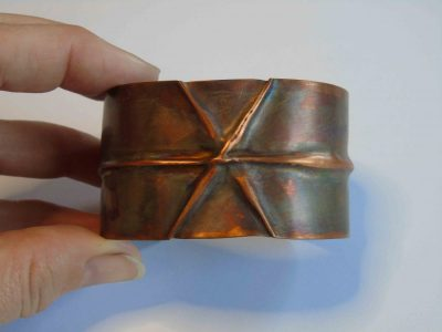 Cuff bracelet with crossing folds