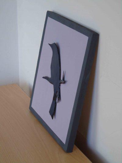 side view of enamelled blackbird on painted wooden board