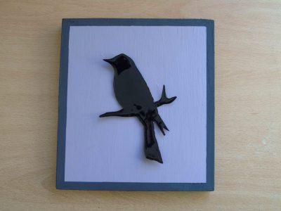 Black blackbird silhouette on mauve wooden frame