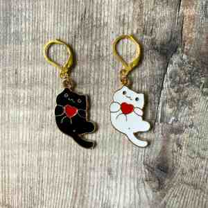 Two stitch markers, one black cat and one white, both holding a red heart