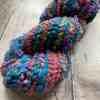 Self-striping core spun art yarn on wood base