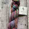 Skein of hand spun thick and thin art yarn on wooden background. Spun by Eleanor Shadow.