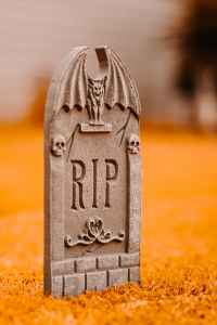 gray tombstone on grass in yard
