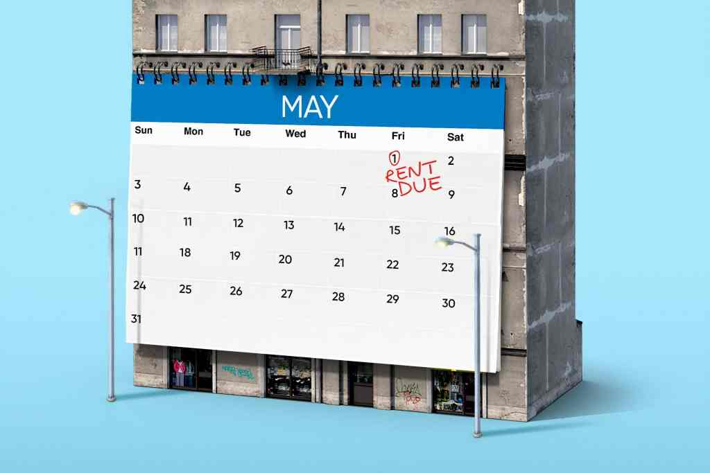 """A calendar hangs on the side of a model building. It's open to the month of May, with May 1st circled in red pen and the words """"Rent Due"""" written on that date."""