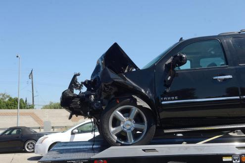 A damaged Chevy Tahoe sits on tow truck after a collision in the HOV lane on the northbound 405/22 Freeway in Seal Beach after a fatal traffic accident on Monday. According to CHP, the accident happened when a Chevy Tahoe crossed the double yellow lane and entered the number two HOV lane. The Tahoe rear ended a Tesla which was pushed in to a Honda Civic. Two young girls were in the back seat of the Tesla. A 7-year old was killed and a 13-year old was injured and is in critical condition. ///ADDITIONAL INFORMATION: Slug: TrafficFatailty.0816.jag, Day: Monday, August 15, 2016 (8/15/16), Time: 11:01:31 AM, Location: Seal Beach, California - Traffic Fatality - JEFF GRITCHEN, STAFF PHOTOGRAPHER