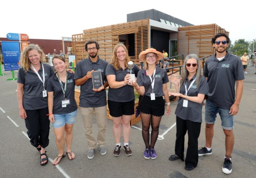 Third place overall winners California Polytechnic State University, San Luis Obispo team members in front of their house. (l-r) Sandy Stannard, Christina Paguin, Brian Murrillo, Lisa-Marie Mueller, Alyssa Parr & Christine Theodoropoulos , Dean of the California Polytechnic State University, San Luis Obispo College of Architecture & Environmental Design at the U.S. Department of Energy Solar Decathlon 2015, October 17, 2015 at the Orange County Great Park, Irvine, California (Credit: Thomas Kelsey/U.S. Department of Energy Solar Decathlon)