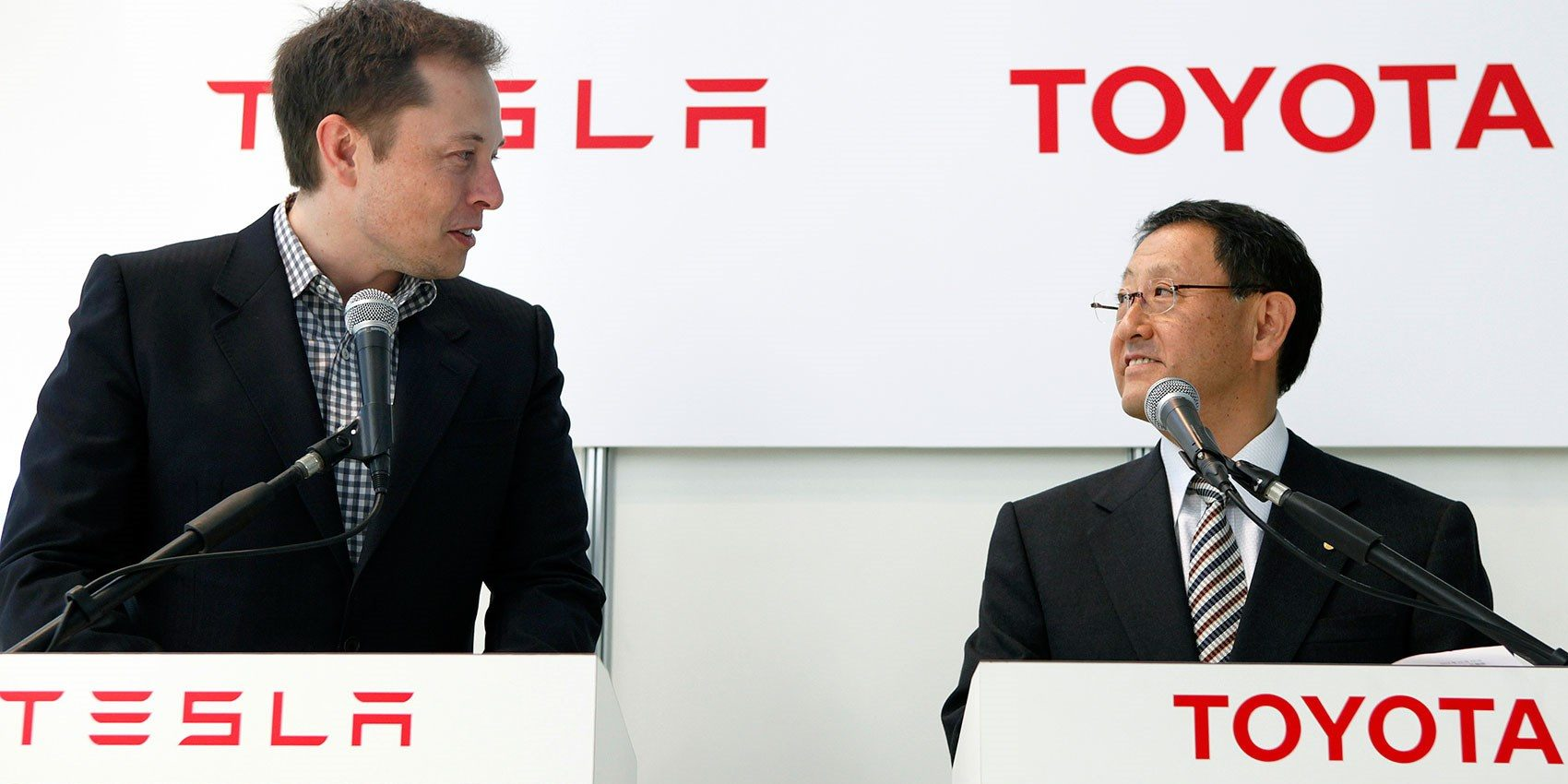 Musk and Toyoda speaking at a conference.