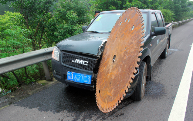 Image of a truck in China struck by a giant, runaway saw blade.