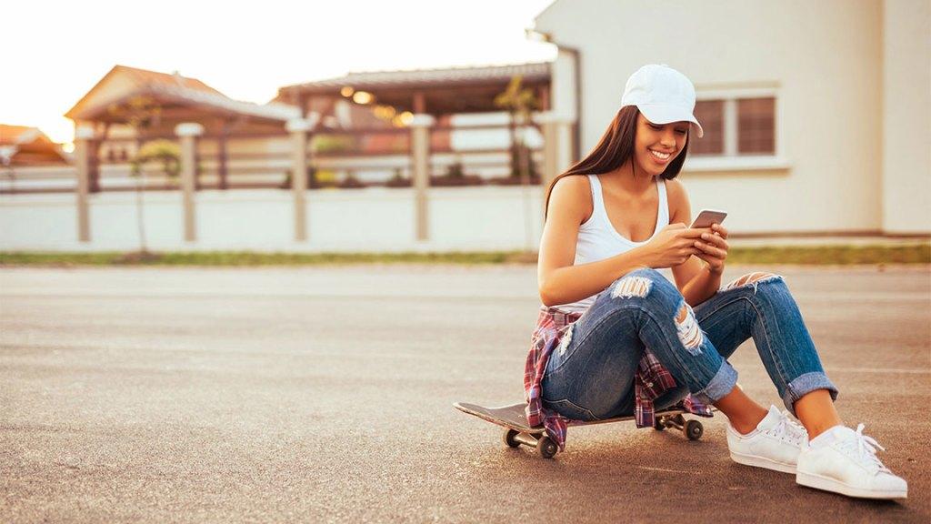girl sitting on skateboard checking social media on her smartphone