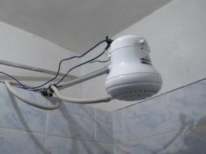 Electricidad con agua. Foto de ducha eléctrica cuyos cables están incorrectamente conectados por fuera.