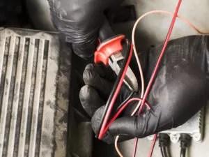 Cómo hacer un empalme eléctrico domiciliario. Foto en primer plano de las manos de un electricista, con guantes, cortando cables con un alicate.