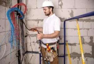 Cómo hacer una derivación eléctrica. Foto de un electricista con sus herramientas profesionales, cortando un cable de una instalación eléctrica.