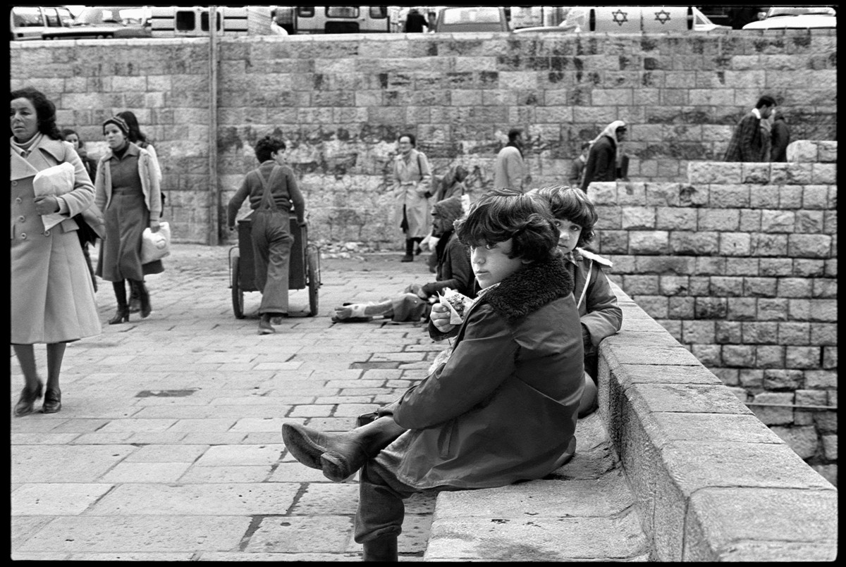 Two children sit on stone bench in front of Damascus Gate