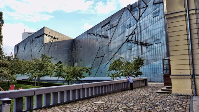 A man is dwarfed by a building that has many angles in its glass facade.