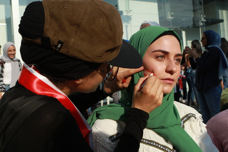 A woman is drawing red lines on the cheek of another woman.