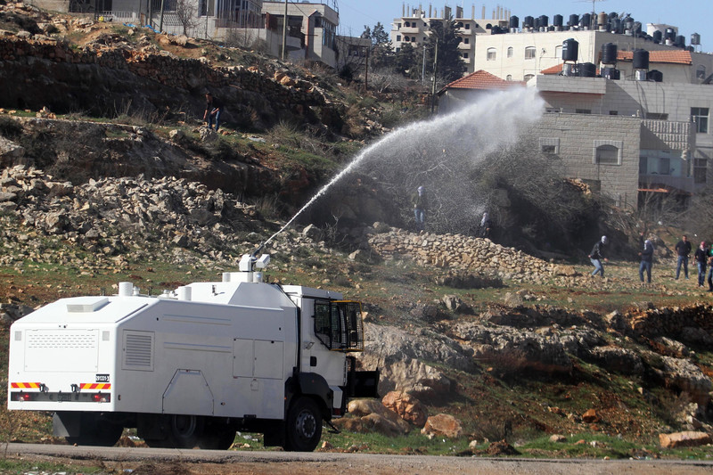 A white armored vehicle sprays liquid at some people on a hillside in the distance