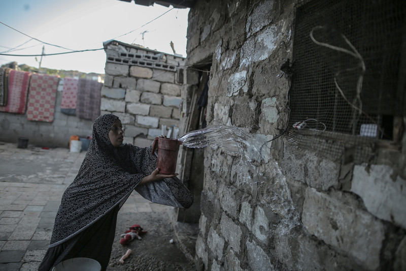 A woman throws a bucketful of water onto a wall