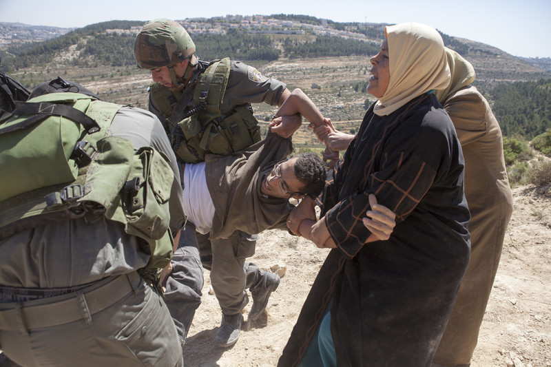 A young man is carried by soldiers and pulled by two civilian women